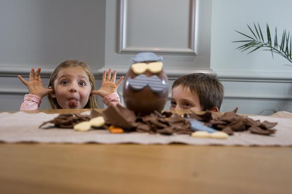deux enfants cachés derrière une table l'un deux fait une grimace devant un oeuf de chocolat
