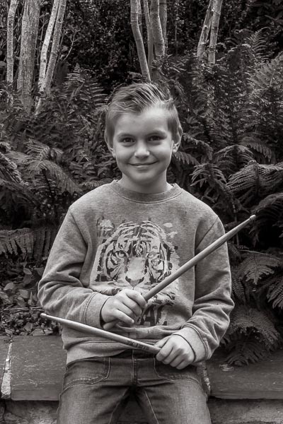 Photo d'un enfant avec ses baguettes de batterie