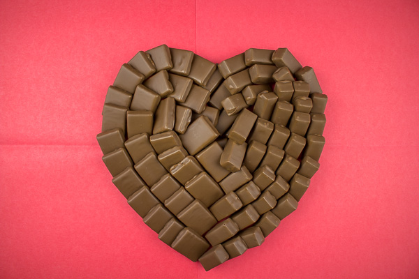 Coeur en chocolat réalisé avec 2 chocolats différents le tout sur un fond rouge