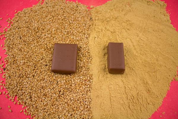 Coeur réalisé avec des graines de sésame et de la poudre de gingembre, 1 chocolat différent posés sur chaque matière le tout sur fond rouge