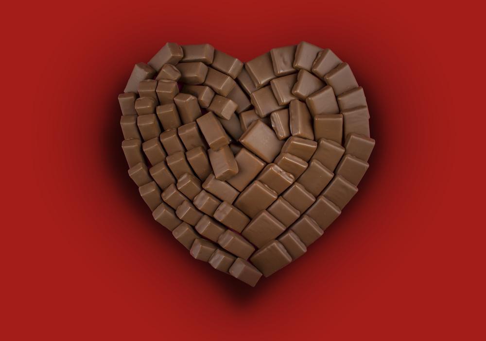 Photo d'un coeur réalisé avec 2 chocolats différents sur un fond rouge (retouchée)