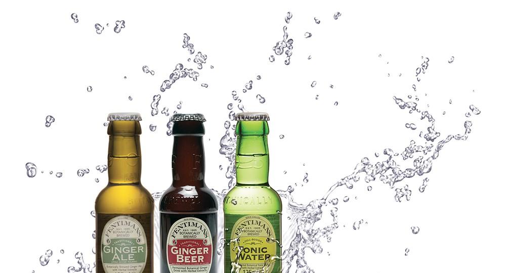 Photo de 3 petites bouteilles de cocktail sur fond blanc avec un effet d'eau